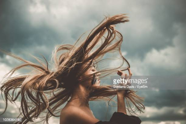 side view of young woman with tousled hair standing against cloudy sky - blowing stock pictures, royalty-free photos & images