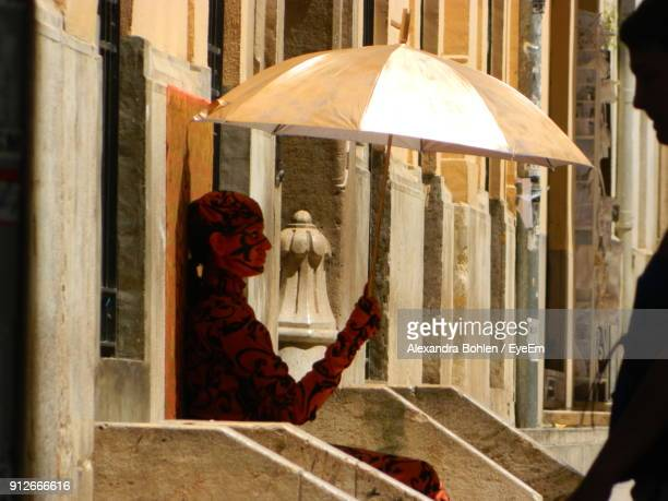 Side View Of Young Woman With Umbrella Sitting On Steps By Building In City