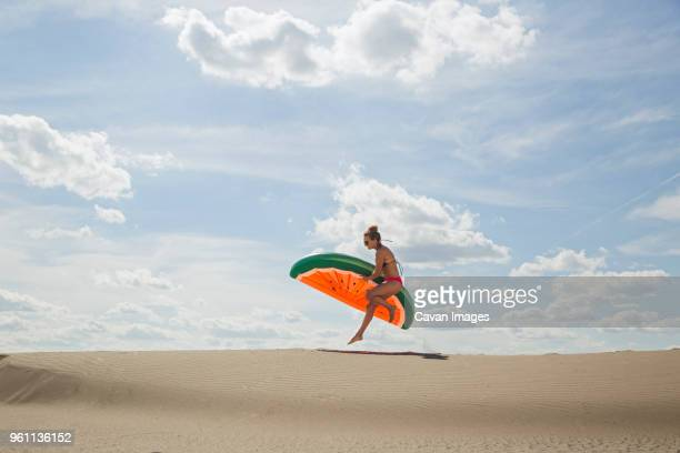side view of young woman with watermelon inflatable ring jumping on sand at beach - inflatable stock pictures, royalty-free photos & images