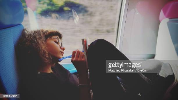 side view of young woman writing on train - train interior stock photos and pictures
