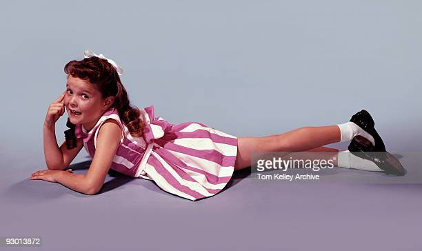 Side view portrait of a young red haired girl looking at the camera while lying down on her stomach 1956 She is wearing a pink striped dress white...