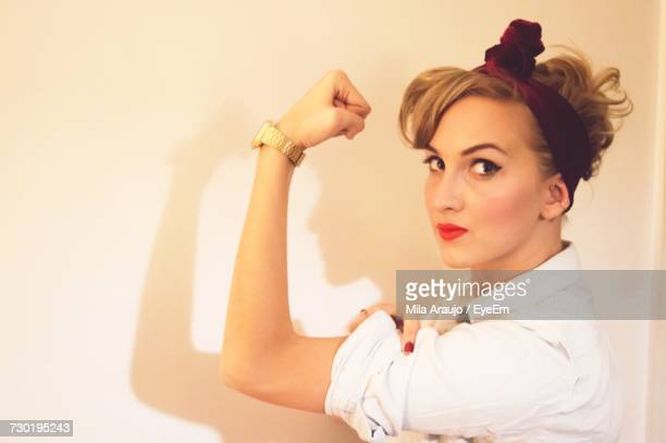 Side View Portrait Of Beautiful Woman Flexing Muscles By White Wall
