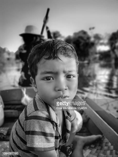 side view portrait of boy sitting on rowboat in river - traditionally cambodian stock pictures, royalty-free photos & images