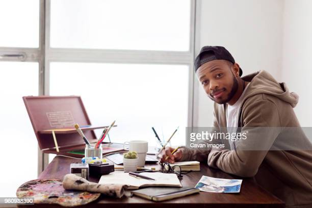 side view portrait of confident painter sitting at desk in creative office - illustrator stock photos and pictures
