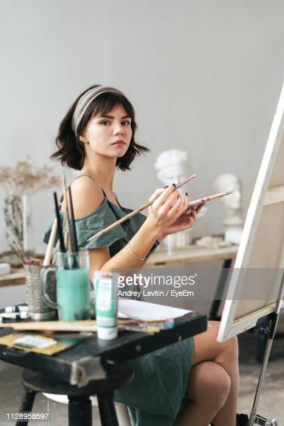side view portrait of confident woman holding paintbrush and palette at art studio - short hair stock pictures, royalty-free photos & images