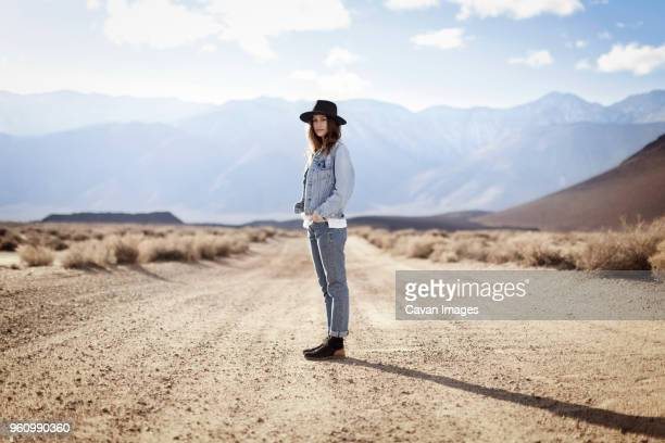 side view portrait of confident woman standing on dirt road against mountains - rocky mountains north america stock pictures, royalty-free photos & images