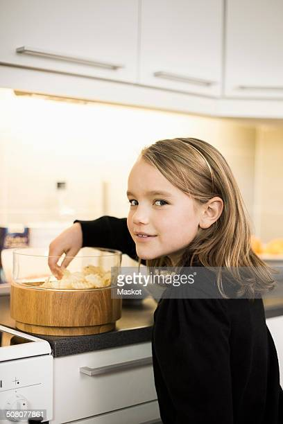 Side view portrait of girl eating potato chips at kitchen counter