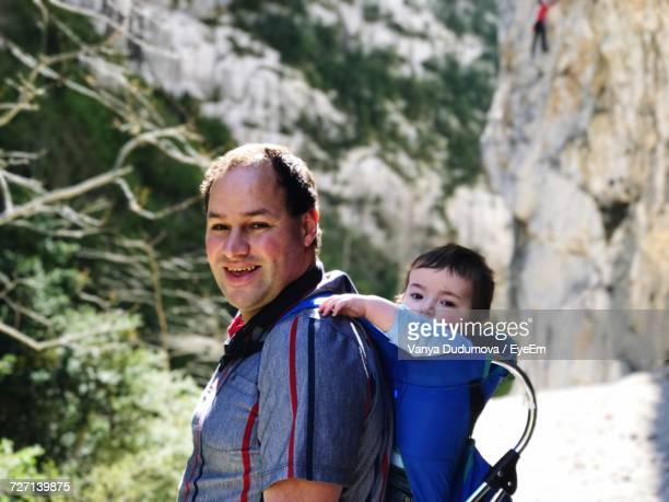 Side View Portrait Of Happy Father Carrying Son In Baby Carrier Against Mountains