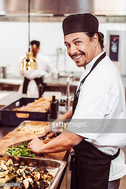 Side view portrait of happy male chef cutting leafy vegetables at commercial kitchen