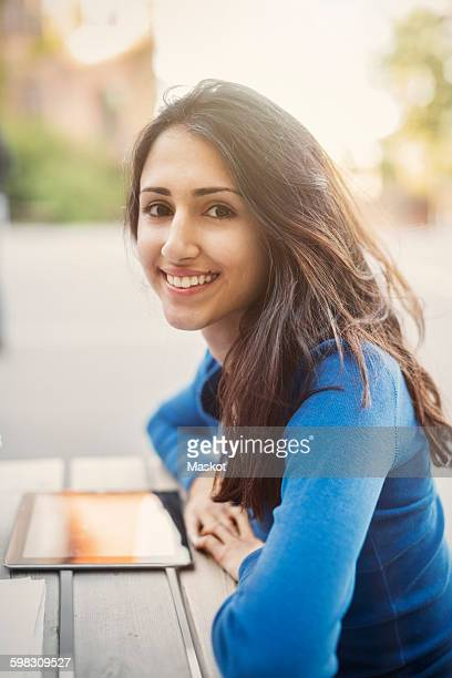 Side view portrait of happy teenager leaning on table outdoors