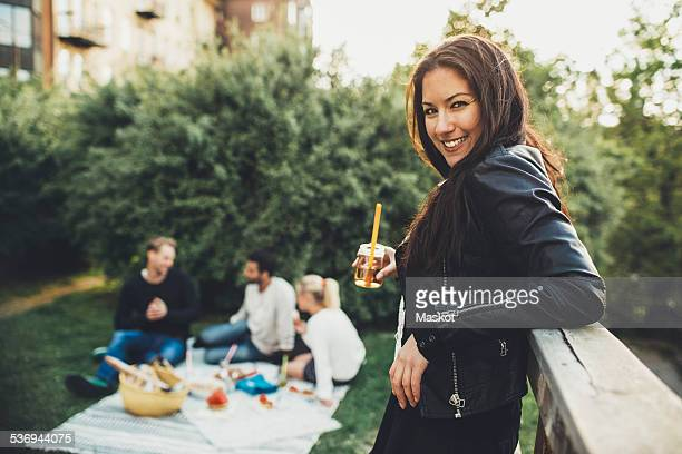 Side view portrait of happy woman holding elderflower drink during rooftop party with friends