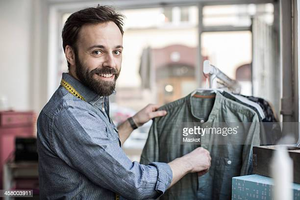 Side view portrait of mid adult male design professional analyzing shirt at studio