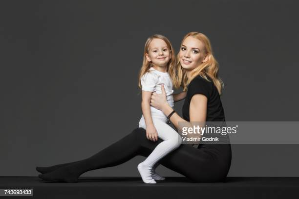 Side view portrait of mother and daughter sitting against gray background