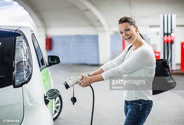 Side view portrait of playful woman electrical charger pump at gas station