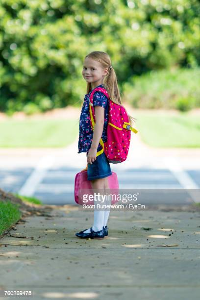 side view portrait of schoolgirl with pink backpack standing on footpath - schoolgirl stock pictures, royalty-free photos & images