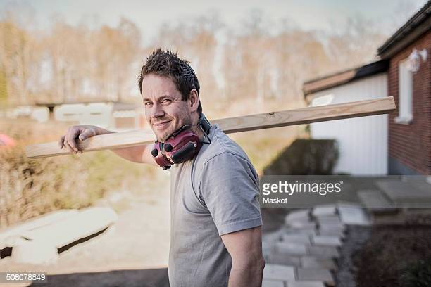 side view portrait of smiling carpenter carrying wooden plank at construction site - noord europa stockfoto's en -beelden