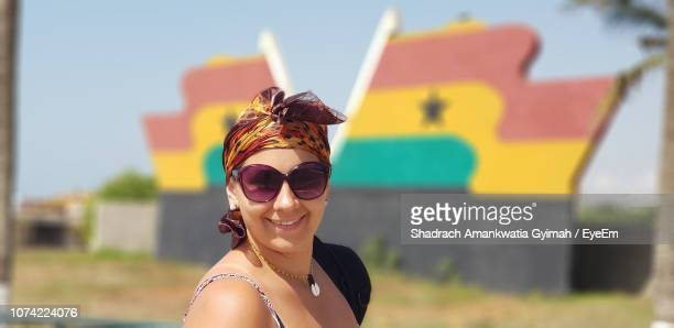 side view portrait of smiling woman wearing sunglasses against ghanaian flag - ghanaian flag stock photos and pictures