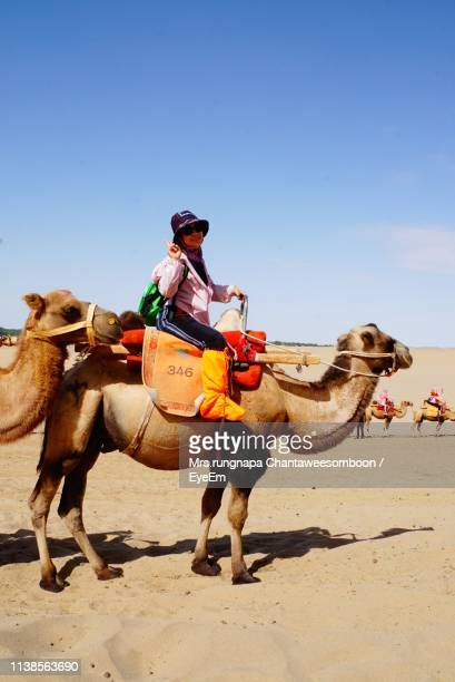 Side View Portrait Of Woman Riding Camel At Desert Against Blue Sky