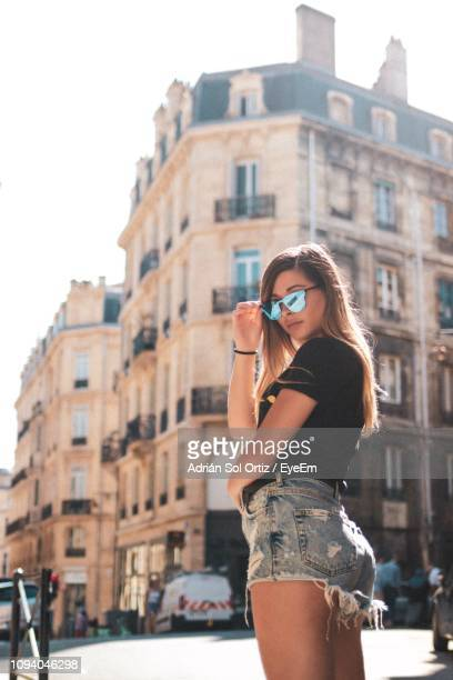 side view portrait of woman standing against buildings in city during sunny day - gironde stock pictures, royalty-free photos & images