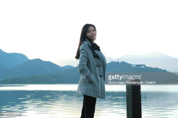 Side View Portrait Of Woman Standing At Lakeshore Against Clear Sky