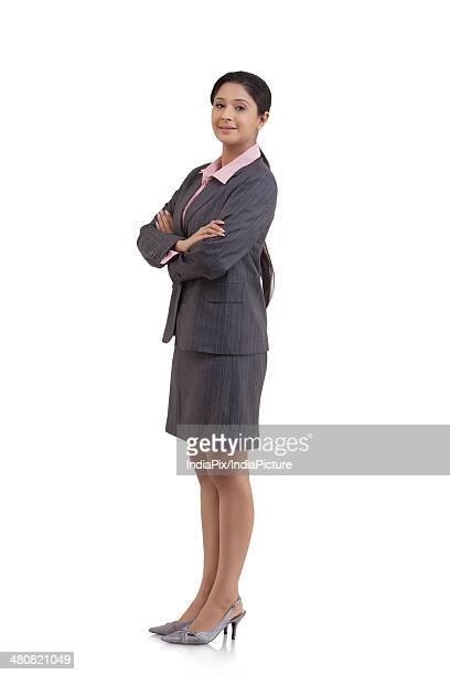 Side view portrait of young businesswoman standing arms crossed over white background
