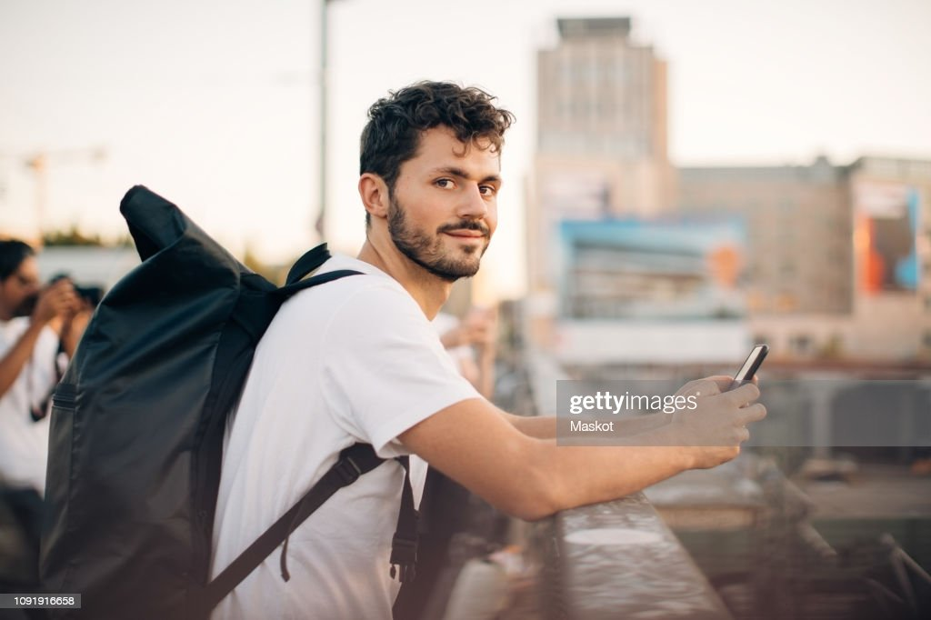 Side view portrait of young man holding mobile phone while leaning on railing at bridge : Stock-Foto