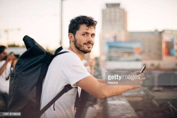 side view portrait of young man holding mobile phone while leaning on railing at bridge - tourist fotografías e imágenes de stock