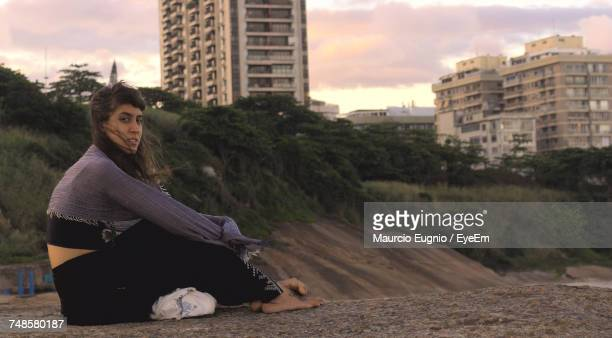 side view portrait of young woman resting on retaining wall during sunset - südamerika stock-fotos und bilder