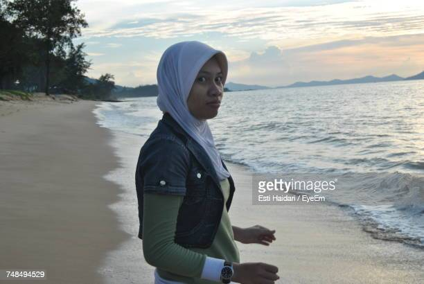 side view portrait of young woman standing on shore during sunset - muslim woman beach stock photos and pictures
