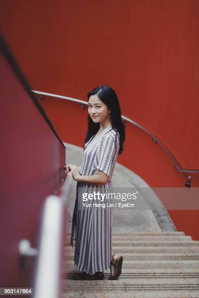 Side View Portrait Of Young Woman Standing On Steps