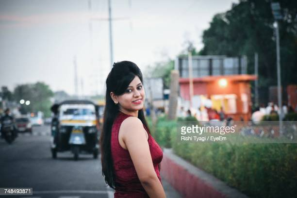 Side View Portrait Of Young Woman Standing On Street In City