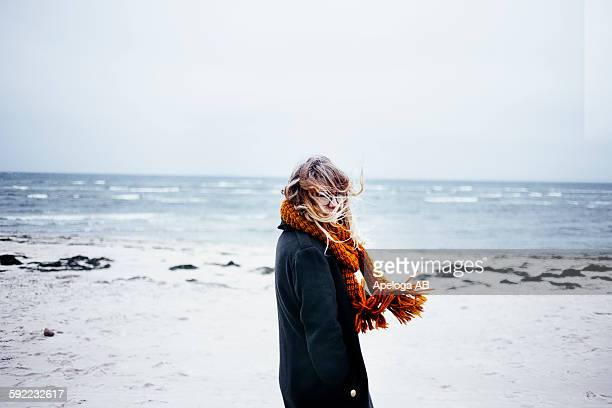Side view portrait of young woman wearing scarf at beach