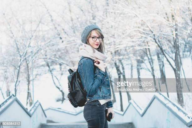 Side View Portrait Of Young Woman With Bag Wearing Warm Clothing During Winter