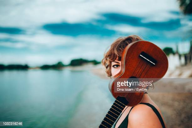 side view portrait of young woman with ukulele at lakeshore - ukulele stock pictures, royalty-free photos & images