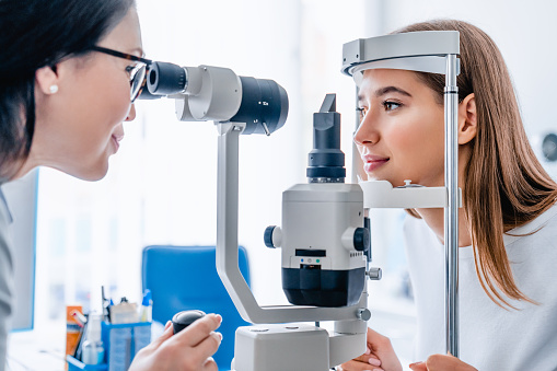 Side view shot of female doctor and patient in ophthalmology clinic 1189208254