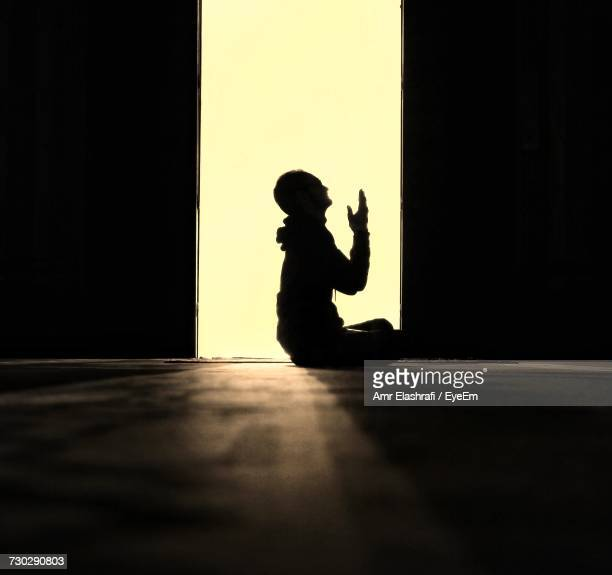 Side View Silhouette Of Man Praying In Mosque