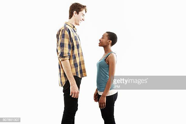 side view studio portrait showing contrasting height of young couple - tall high stock photos and pictures