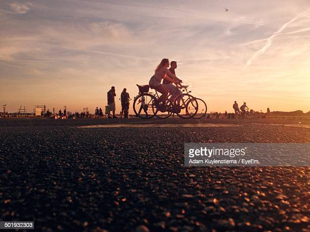side view surface level of people bicycling against sky - tempelhof airport stock pictures, royalty-free photos & images