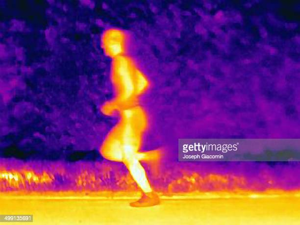 Side view thermal photograph of young male athlete running. The image shows the heat of the muscles