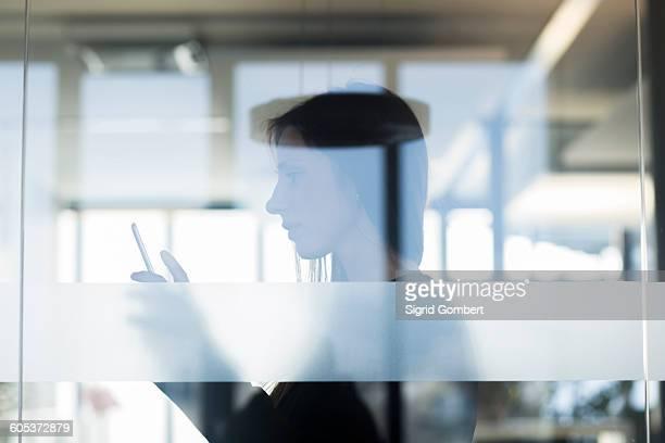 side view through window of young woman holding digital tablet - sigrid gombert stockfoto's en -beelden
