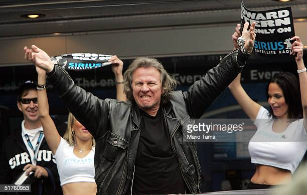 Sidekick Fred Norris waves as Radio personality Howard Stern prepares to hand out free satellite radios with Scores dancers in the background to...