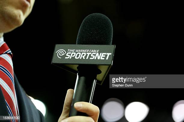 A sideline reporter holds a microphone with the logo of Time Warner Cable Sportsnet during the game between the Golden State Warriors the Los Angeles...