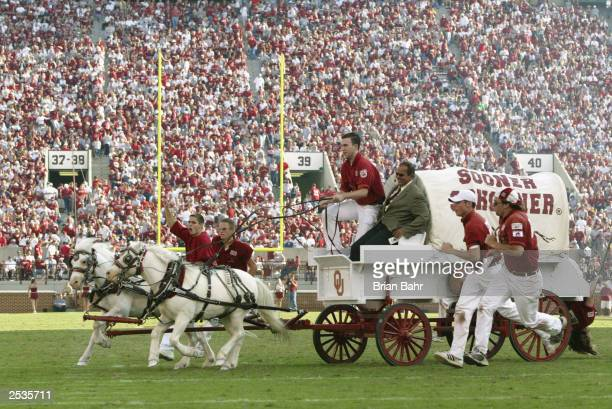 Sideline reporter Jack Arute takes a ride on the University of Oklahoma Sooners Boomer Schooner after a touchdown during a game against the...