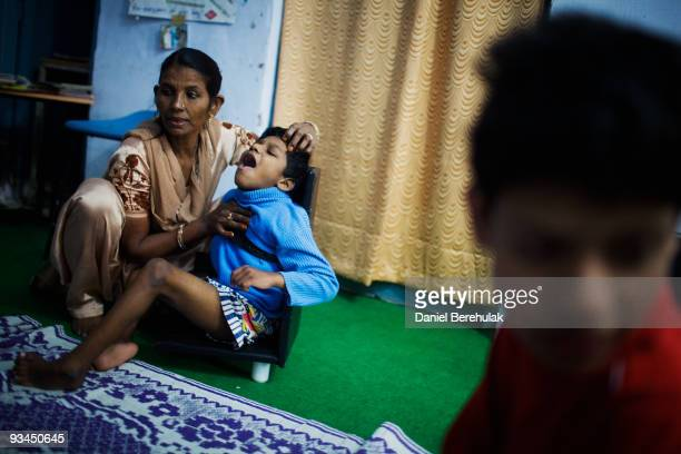 Sidesh Kumar suffering from epilepsy is comforted by Nafiza Bee co-ordinator of the Chingari Trust clinic on November 27, 2009 in Bhopal, India....