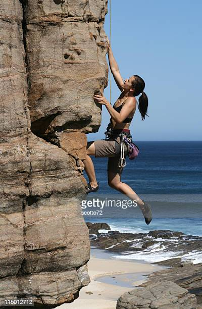 Side-view of a woman climbing a rocky cliff