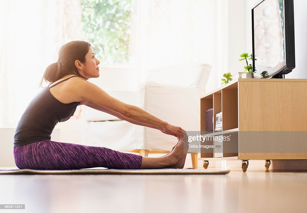Side-view of woman exercising in living room : Foto de stock