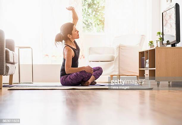 side-view of woman exercising in living room - television show stock pictures, royalty-free photos & images