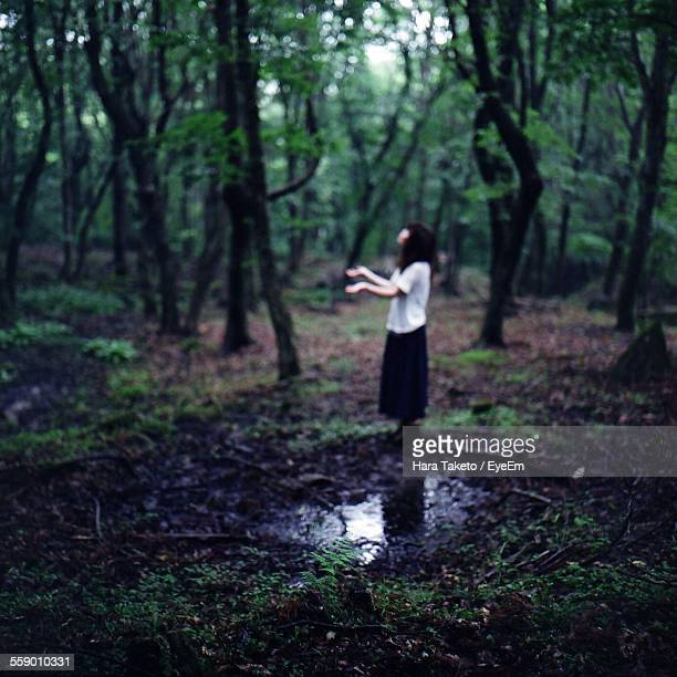 Side-View Of Young Woman Gesturing In Forest