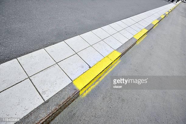Sidewalk and yellow road markings