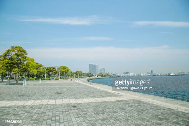 sidewalk by buildings in city against sky - 公園 ストックフォトと画像